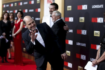 "Show creator Matthew Weiner waves while Jon Hamm and Robert Morse pose together in the background at the ""Mad Men"" Black and Red Ball to celebrate the final seven episodes of the AMC television series in Los Angeles"