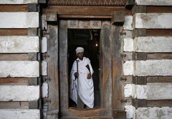 An Ethiopian Orthodox priest walks out of the Yemrehana Krestos church in Lalibela