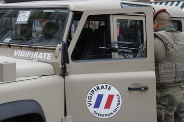 """A French army paratrooper enters a car marked """"Vigipirate"""" while on patrol in Paris"""