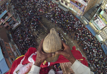 Chakala Dangol, 75, holds a coconut in his hands before throwing it towards the devotees from the top of the chariot of Rato during the chariot festival in Lalitpur