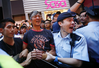 Police remove a man, who a witness said started a fight with several pro-democracy protesters, after the protesters tied his hands near a barricade on a main street in Hong Kong's Mongkok shopping district