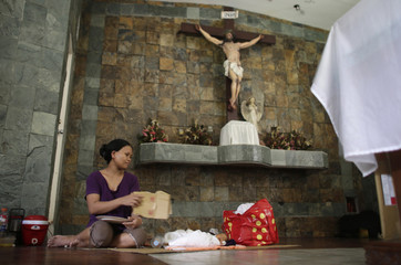 A mother fans her baby lying on the floor inside a chapel which was turned into a makeshift hospital after Typhoon Haiyan battered Tacloban city in central Philippines