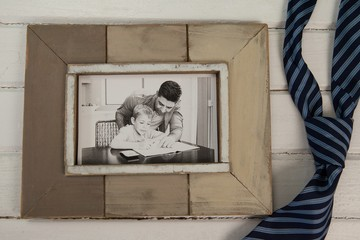 Photo frame and tie on wooden plank
