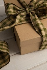 Tied gift box on wooden plank