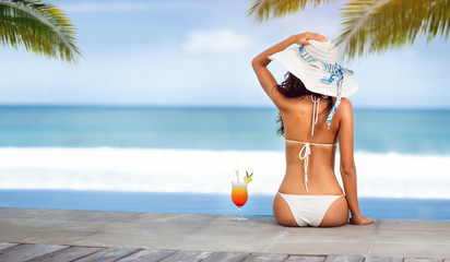 Woman in hat near the sea on beach with tropical cocktail
