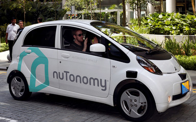 File photo of a safety driver putting up his hands as his driverless car navigates a road in Singapore
