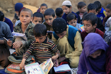 Students attend a class at a makeshift school on the outskirts of Islamabad