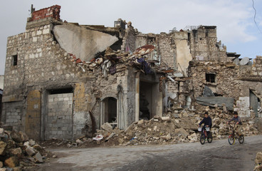 Boys ride bicycles past a damaged building at the Bab al-Nasr neighbourhood of Aleppo