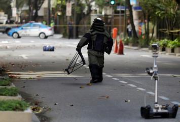 A Brazilian police officer from the anti-bomb squad checks suspect bomb near Leblon beach ahead of the 2016 Rio Olympic games in Rio de Janeiro
