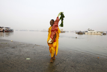 A Hindu priest carries banana tree trunks after taking a dip in the waters of the Ganges river during a ritual as part of the Durga Puja festival in Kolkata