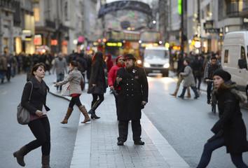 Pedestrians walk along Oxford street in central London