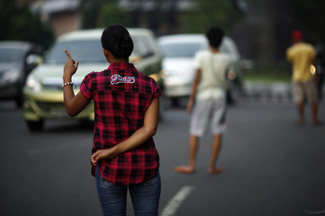 """A jobless woman offers to be a """"car jockey"""" in a main street in Jakarta"""