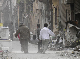People walk as they carry an injured man on a stretcher in the besieged area of Homs