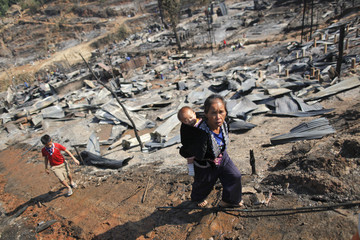 A refugee woman from Myanmar carries her baby through ruins of the Um-Piam refugee camp after a fire engulfed a big part of it near Mae Sot