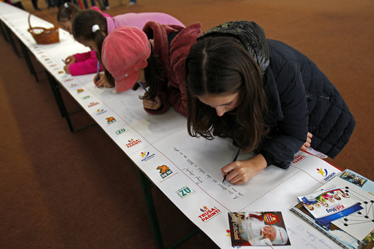 Children write Christmas wishes on world's longest letter addressed to Santa Claus during a Guinness World Record attempt in Pantelimon
