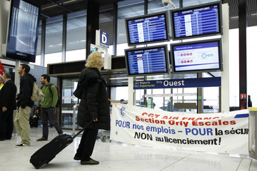 A traveller pulls her bag as she looks at flight departure screens above a protest banner during a strike by Air France employees at Orly Airport