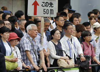 People listen to an election campaign speech by Japan's Prime Minister Shinzo Abe, who is also leader of the ruling Liberal Democratic Party, during a campaigning for the July 21 Upper house election in Tokyo