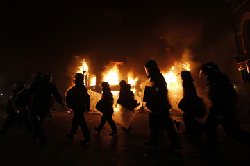 Police officers wearing riot gear walk past a burning building in Tottenham