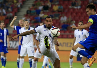 Greece's Mitroglou fights for the ball with Finland's Sparv during their Euro 2016 group F qualification match at the Karaiskaki stadium in Piraeus, near Athens