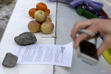 Woman takes picture of cigarette, letter and fruits delivered by Chinese Google users as a symbol of goodbye in Beijing