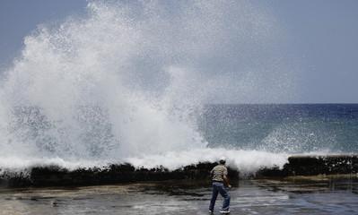 A man watches waves crash against Havana's seafront boulevard 'El Malecon'