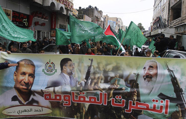 Palestinians wave Hamas flags during a rally celebrating what they claim to be Hamas' victory over Israel in the Gaza conflict, in Ramallah
