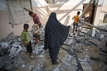 Palestinians walk over rubble from a home in Gaza City