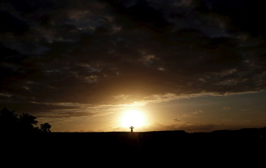 A man takes a picture of the sunset on a beach in Salvador da Bahia