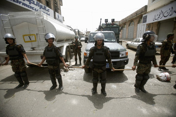 Riot policemen stand guard outside the French embassy in Sanaa