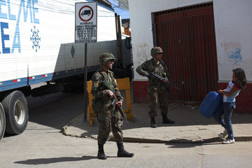 An earthquake survivor carries a water jug past soldiers guarding the city center in Constitucion