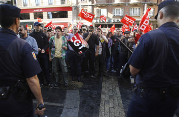 Picketers confront police officers during a nationwide general strike in central Madrid