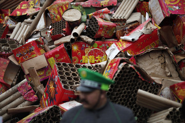 Discarded fireworks packaging is pictured in the background during an event organized by Chinese multimillionaire Chen Guangbiao in Nanjing