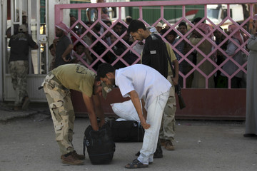 A Free Syrian Army member checks a man's baggage at the Syrian border crossing of Bab al-Hawa, in Harem, Idlib Governorate
