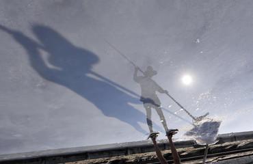 A worker harvests sea salt in the Secovlje salterns