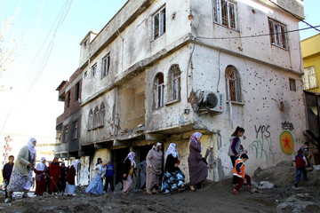 Women walk past a building, which was damaged during the security operations and clashes between Turkish security forces and Kurdish militants, in Silvan, in the Kurdish-dominated southeastern Diyarbakir province, Turkey