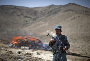 An Afghan policeman keeps watch in front of a pile of burning illegal narcotics in Kabul