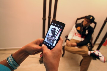 A woman takes a picture of the dead body of Fernando de Jesus, who was killed when shot repeatedly by unknown assailants, at a funeral parlor in San Juan