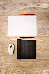 graphic tablet, computer mouse, sheet of paper and marker on the table, top view