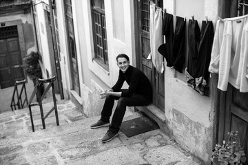 Young fashionable guy on the streets of a European town, sitting on the porch of the house. Black-and-white photo..