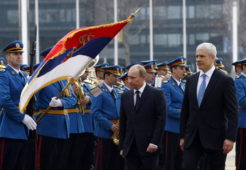 Serbia's President Tadic and Russia's Prime Minister Vladimir Putin review an honour guard during Putin's visit to Belgrade