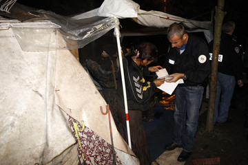 A French policeman checks passport of a Roma family before to evacuate an illegal camp in Mons en Baroeul