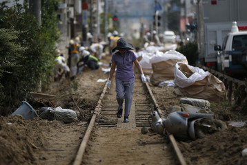 A local resident walks on a damaged railway track at a site where a landslide swept through a residential area at Asaminami ward in Hiroshima