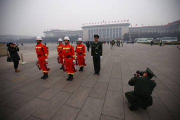 Paramilitary policeman takes pictures of firefighters and another paramilitary policeman on hazy day during Chinese People's Political Consultative Conference in front of the Great Hall of the People at Tiananmen Square in Beijing