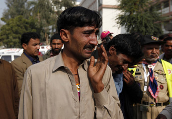 A man mourns the death of his relative who was killed in an accident after a bus and truck collided early Sunday, outside a hospital in Karachi