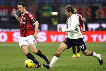 AC Milan's Van Bommell challenges Dessena of Cagliari during their Serie A soccer match at Giuseppe Meazza stadium in Milan
