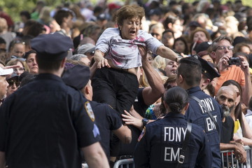 A woman needing medical attention is pulled out of a crowd as thousands await to witness Pope Francis and his motorcade ride through Central Park, Manhattan, New York