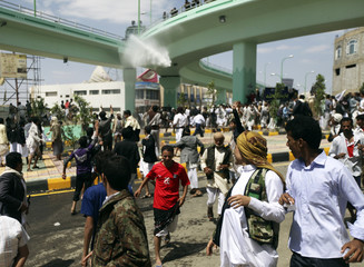Protesters run as police use water cannons to disperse them at a crossroad leading to the U.S. embassy in Sanaa