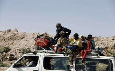 People ride atop a van as they flee their homes in an area where a rocket base was hit with air strikes in Yemen's capital Sanaa