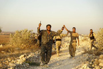 Free Syrian army fighters gesture as they celebrate after they took control of Tal al-Zaatar city, activists said, in the province of Deraa