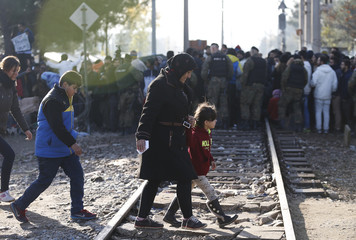 Migrants walk after crossing the border from Greece into Macedonia, near Gevgelija